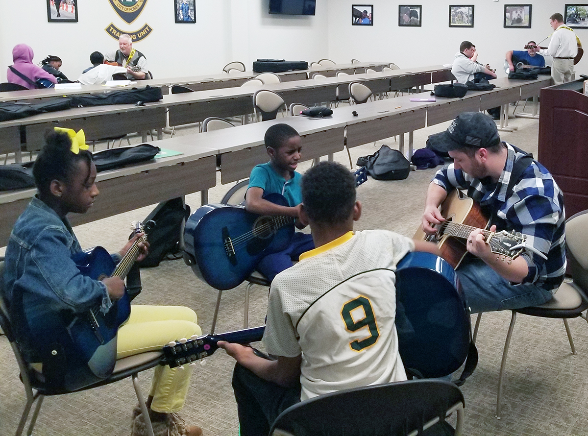 "Newnan ""Guitars Not Guns"" students and instructors practicing at the city's police department."